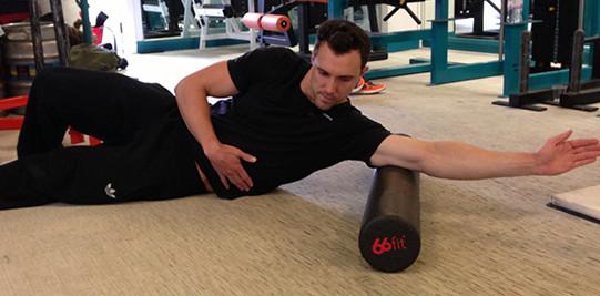 man rolt zijn triceps met een foam roller